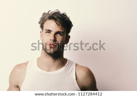 Masculinity, temptation and confidence concept. Man with fair hair on white background, copy space. Macho with seductive face and confident look. Guy with strong muscles in white tank top.