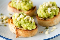 Mashed avocado on toasted baguette bread topped with bean sprouts. Healthy vegan appetizer or snack
