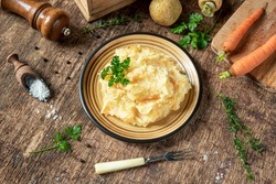 Mashed parsnips with potatoes and carrots and ingredients for making tasty parsnip puree on a dark wooden background. Delicious and healthy vegetarian food rich in vitamins and minerals.