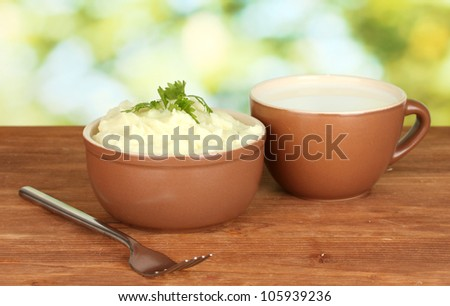 Mashed potato with parsley in the bowl and cup with milk on wooden background - stock photo