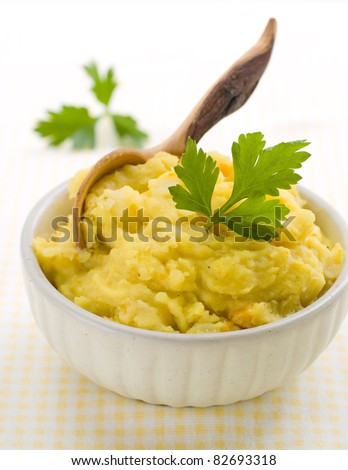 Mashed potato with wooden spoon, in serving bowl. Selective focus