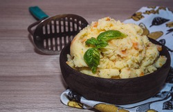 Mashed potatoes and carrots in a wooden bowl isolated on a wooden background. Side view, copy space.