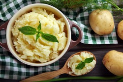 Mashed potatoes in bowl on wooden table with checkered napkin, top view