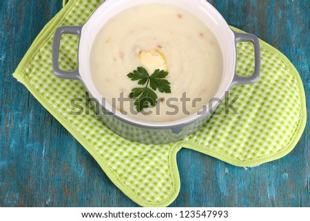 Mashed potatoes in saucepan on blue wooden table - stock photo