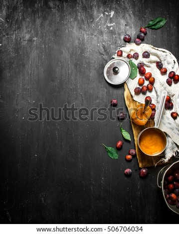 Mashed ripe plums in a small saucepan. On a black chalkboard. #506706034