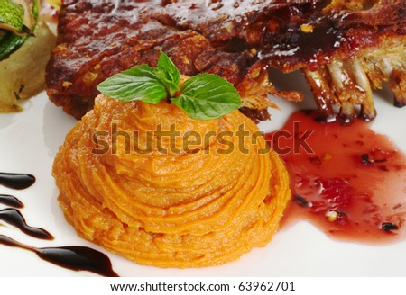 Mashed sweet potato garnished with mint leaf and rib with a red sauce (Selective Focus, Focus on mint leaf as well as top and front of sweet potato puree)