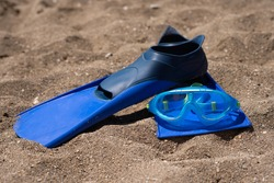 Mask and flippers on the beach. Sports accessories for swimming. Underwater masks and flippers