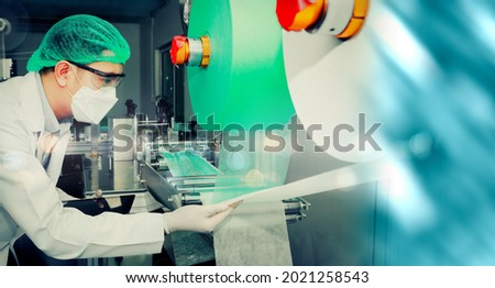 Mask factory : Male experts wearing masks care automatic mask production machines stand to inspect the rolls of cloth material to produce masks on the conveyor belt for fast continuity efficiency Stok fotoğraf ©