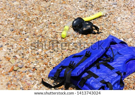 Mask for scuba diving with a tube lying on the beach near the blue life jacket. The concept of Safety on the water. #1413743024