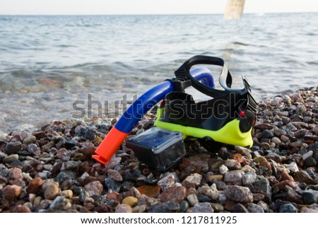 mask for scuba diving with action camera on rocky beach near the sea. Relax by the sea. Summer vacation. snorkeling #1217811925