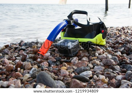 mask for scuba diving with actoin camera on rocky beach near the sea. Relax by the sea. Summer vacation. snorkeling #1219934809