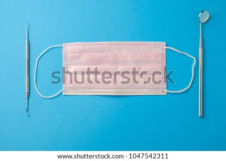 Mask of the dentist on a blue background, mirror and feeler, top view