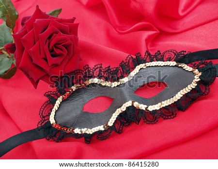 mask with the rose on the red silk