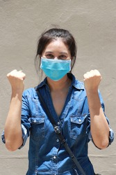 Masked Asian woman prevent germs and wear denim skirt dress. Tiny Particle or virus corona or Covid 19 protection. Lift the fist up for meaning fighting or concept of Combating illness.