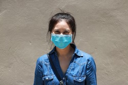 Masked Asian woman prevent germs and wear denim skirt dress. Tiny Particle or virus corona or Covid 19 protection. Concept of Combating illness.