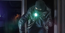 Masked burglar with crowbar breaking and entering into a house - shot with dramatic motion