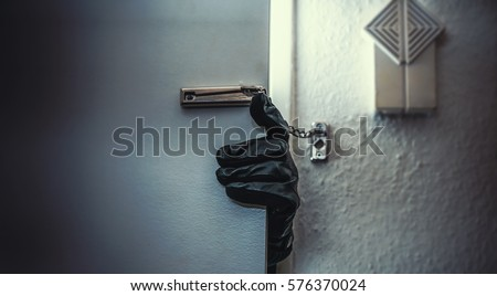Photo of  masked burglar with crowbar breaking and entering into a victim's home