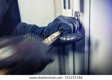 masked burglar with crowbar breaking and entering into a victim's home - shot with dramatic motion Stockfoto ©