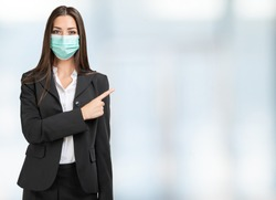 Masked business woman pointing her finger to a bright space