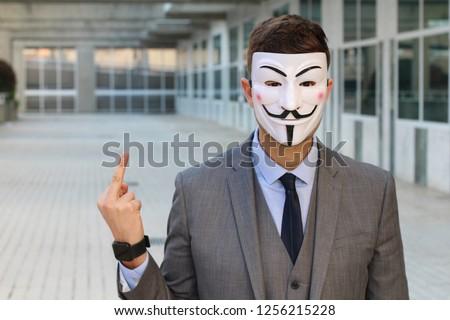 Stock Photo Masked businessman showing middle finger