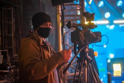 masked cameraman is filming a television show in the studio. TV