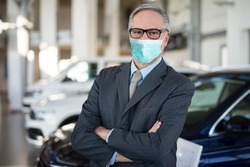 Masked car dealer principal inside showroom during coronavirus pandemic