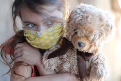 Masked Child with Favorite Doll Teddy Bears. Portrait Sad Little Girl. Serious Baby. Protective Mask. Preventive measures against covid-19, viruses, flu. Basic hygiene rules. Pandemic. Stay at Home