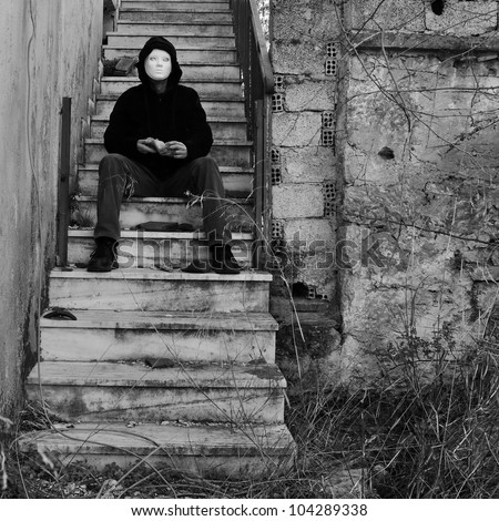 Masked figure with doll hand sitting on abandoned house staircase. Black and white.