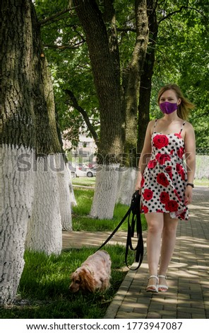 masked girl walking a dog in the park during quarantine