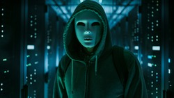 Masked Hacker in a Hoodie Standing in Corporate Data Center with Rows of Working Rack Servers.
