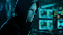 Masked Hacktivist Organizes malware Virus Attack on Global Scale. Hacker in Underground Secret Location Surrounded by Displays and Cables.