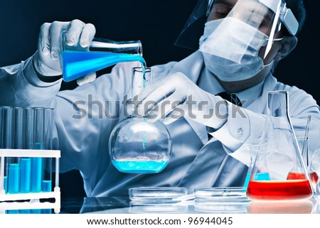 Masked male scientist mixing bright blue substances in glassware