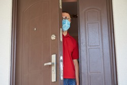 masked man looks out the door,a man in a red shirt and medical mask looks out through the slit of the door to the street