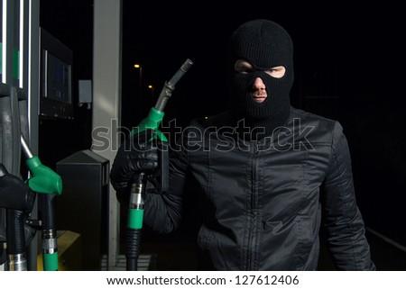 masked man using gas pump
