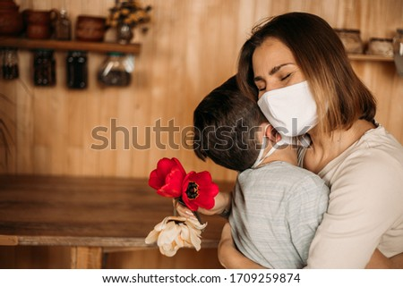Masked mom hugs masked son. Happy family in quarantine. Love mom and son