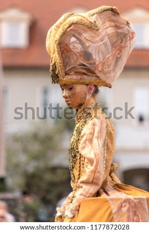 masked woman dressed in gold in Venetian carnival costume #1177872028