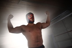 Masked wrestler flexing muscles