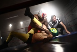 Masked wrestlers and referee in ring