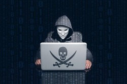 Masking anonymous hacking and using computer to hack passwords. Dark background and binary 0 and 1
