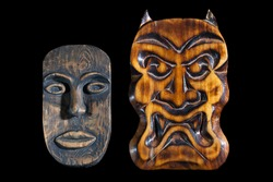 Masks carved from wood on a black background. African mask and the mask trait