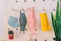 Masks of many colors for corona virus prevention hanging on wall at home or store. Pastel color for cute face mask fashion style. Wooden background with plants.