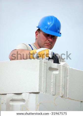 Mason applying mortar using trowel onto house wall brick layer