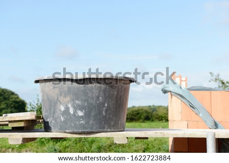 mason bucket and building stones on construction site on wooden scaffolding