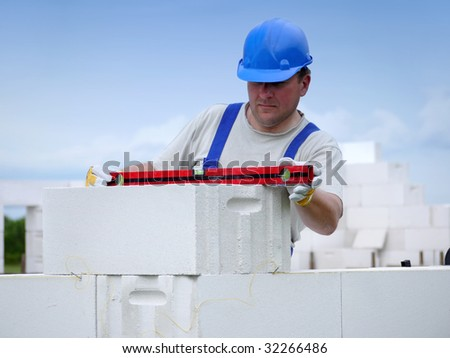 Mason checking horizontal level of house wall  layer being made from aerated autoclaved concrete blocks