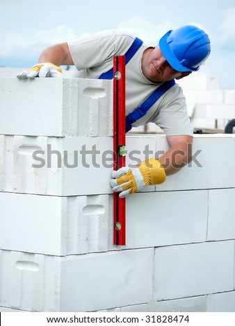 Mason checking plumb line of house wall being made from aerated autoclaved concrete blocks