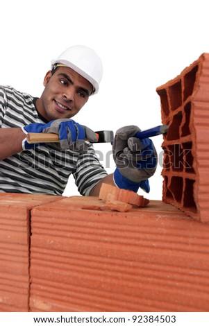 Mason chiseling away at brick