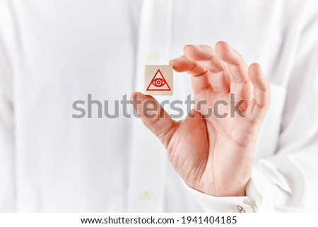 Mason hand holds a wooden cube with the eye of providence or all seeing eye of god symbol. Freemasonry masonic concept. Stock photo ©
