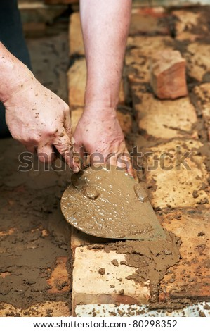 Mason hands at bricklaying works with trowel and clay brick blocks