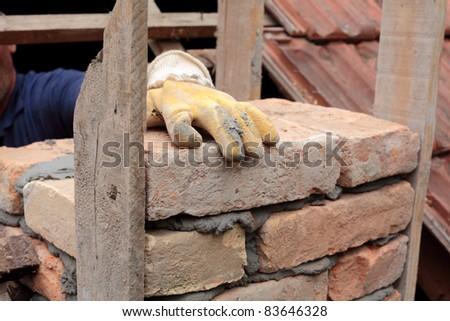 Mason hands making chimney with mortar and bricks