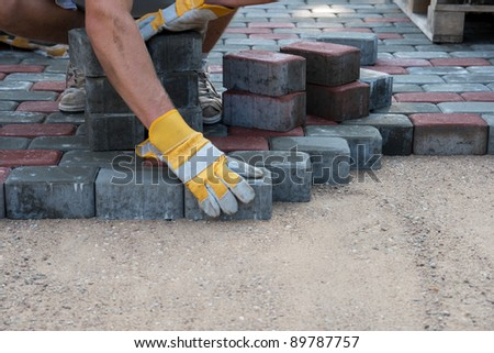 Mason is building pavement. Hands in yellow gloves lays layers of bricks.
